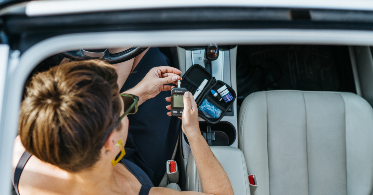 Woman checking her blood sugar in a car