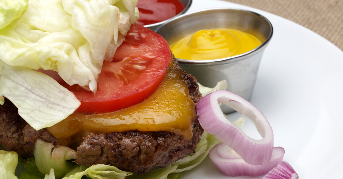 Hamburger wrapped in lettuce with onions, mustard and ketchup on the side