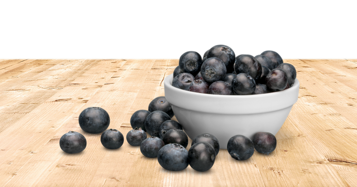 A bowl of blueberries on a wooden table