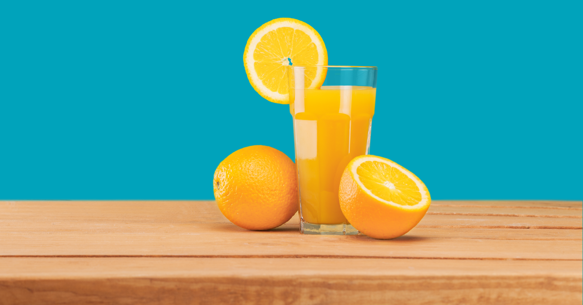 Oranges and a glass of orange juice on wooden table